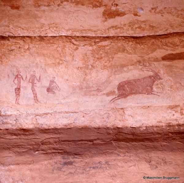 418 Jabbaren (Tassili-n'Ajjer). — Scène de chasse traitée à l'ocre rouge et composée de trois chasseurs à gauche, dont deux lèvent leur arc dans la main gauche, et un autre l'a posé devant lui. Ils sont dans l'expectative alors qu'à droite, une grosse antilope fuit devant eux. Du museau au bras arrière du dernier personnage : 0,80 m.