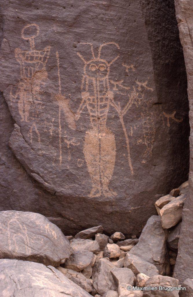 10 Tassirés. Oued Tilemsane (Aïr). — Epoque cabaline. Le personnage du centre à tête dite « de fourmi » typique de cette époque où dominent davantage des guerriers que des chasseurs. On notera le costume, les appendices sur la tête, qui ne sont peut-être pas des plumes. Hauteur du personnage du sommet des antennes aux pieds : 1,50 m.