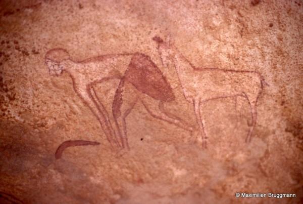 422 Jabbaren (Tassili-n'Ajjer). — Personnage peint en blanc à pagne sombre. Il est suivi par un petit ongulé. On remarque dans ses mains ce qui peut être une faucille » formée d'éclats de silex insérés dans une côte de mammifère. Il porte (?) une sorte de bonnet et une antilope est devant lui. De la queue de la petite antilope au front de l'homme : 0,27 m.