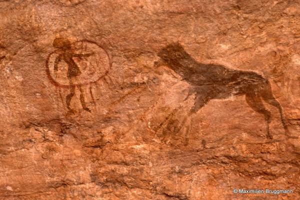 539 Tan-Zoumaïtak (Tassili-n'Ajjer). — Cette peinture à l'ocre rouge nous présente, à gauche, un petit personnage à ample chevelure en partie inséré dans un cercle d'où pendent des lanières. L'animal de droite est peut-être un mouton brun foncé. Le cercle mesure 0,20 m de diamètre.