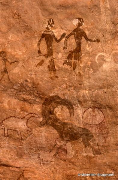 537 Tan-Zoumaïtak (Tassili n'Ajjer). — Les danseuses en tenue d'apparat portent, semble-t-il, des tuniques longues, la bande d'étoffe au niveau de la ceinture étant peut-être un noeud. Si l'on regarde la main droite de la danseuse de gauche, il apparaît qu'elle est posée sur le mouflon de gauche et qu'il y aurait donc contemporanéité entre les danseuses et les mouflons. Noter la structure des calottes et l'original ornement des têtes. Les bras portent de nombreux anneaux.
