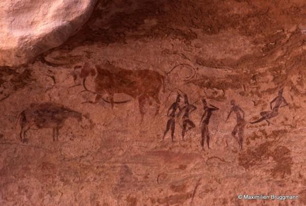 420 Jabbaren (Tassili-n'Ajjer). — Scène pastorale peinte en ocre rouge et blanc. Les personnages du centre ont une coiffure très élevée. Il se peut que ce soient des femmes. Les gestes sont élégants, bien observés. La personne au centre mesure 0,21 m de hauteur.