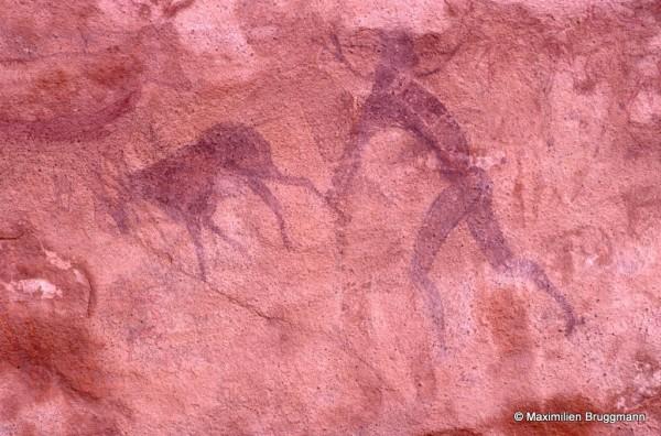 451 Ouan Bender (Tassili-n'Ajjer). — Scène complexe. Il n'est pas possible de « classer » les figura¬tions. Un personnage à « tête ronde » forme l'essentiel du tableau. Il est surchargé à gauche par une gazelle, à droite par un personnage supposé suivre cette gazelle. L'individu mesure, des pieds à la tête, 0,34 m de haut.