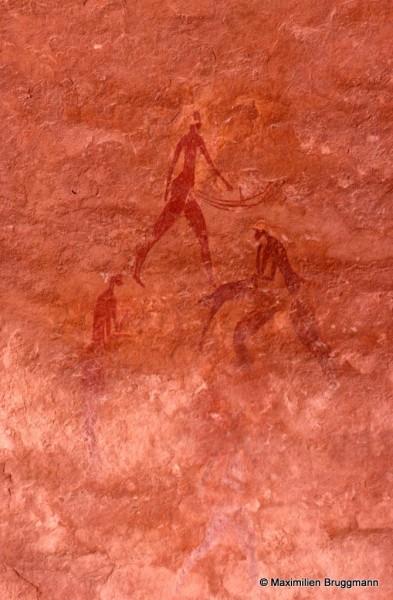 467 Ozeneare (Tassili-n'Ajjer). — Personnage négroïde à coiffure blanche et tenant à la main gauche un objet indéterminé. Du bas ventre partent trois traits incurvés sans explication plausible. Il mesure 0,14 m de hauteur.