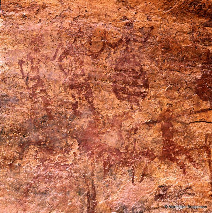 281 Col d'Amoggiar (Mauritanie). — Fresque de personnages peints à l'ocre rouge dans un petit abri sous roche isolé. On devine, en haut à gauche, despersonnages debout ayant chacun la main droite sur la hanche et la gauche tendue vers le voisin. Le deuxième tient un arc de la main droite. Le troisième personnage tient la main du deuxième et porte une sorte de jupe ballon. En dessous, à droite, un cavalier, une personne assise et un petit bovidé. OEuvre très dégradée par l'érosion due au vent.