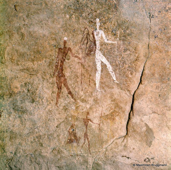 215 Tadrart Acacous. Ouan Amil. — Deux person¬nages. L'un blanc, à droite, avec des cuisses étroites ; l'autre noir avec des cuisses larges et une morpho-logie typiquement négroïde. Ils sont représentés dans la même attitude. L'homme « noir » tient dans la main gauche, un bâton ou une lance. L'homme « blanc » tient un arc, également dans la main gauche. Hauteur de l'homme blanc : 0,23 m.