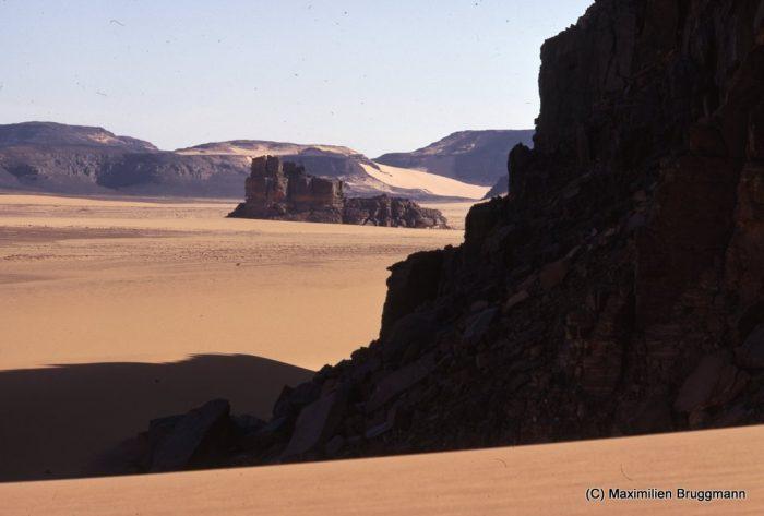 Vue de l'Enneri Blaka. — Arrivant au bord des falaises en vue de l'Enneri, nous avons eu l'impression qu'un kiosque de sous-marin émergeait des sables. Le nom est resté... Et l'illusion est grandele. Le site lui-même a été découvert en 1956 par les officiers méharistes Lamothe et Moreau. En 1959, la mission Berliet-Ténéré y a ajouté les sites 2 et 3. La mission Bruggmann a complété l'inventaireen 1967 par la découverte du site 4. Puis, à la fin de 1968, lors des recherches de la mission Blaka dirigée également par M. Bruggmann, ont été trouvés d'autres sites très intéressants auxquels on a attribué les numéros 5 à 11.