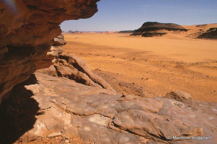 106 Enneri Blaka. Site 5. — Vue typique d'un habitat néolithique dominant la vallée et son cours d'eau. Il s'agit d'un abri sous roche dont le sol garde des meules dormantes, des traces d'aiguisage. Des éclats de céramique sont parsemés au pourtour de l'abri. L'abri mesure 19 m de large, 7 m de profondeur et le plafond est à 3 m.