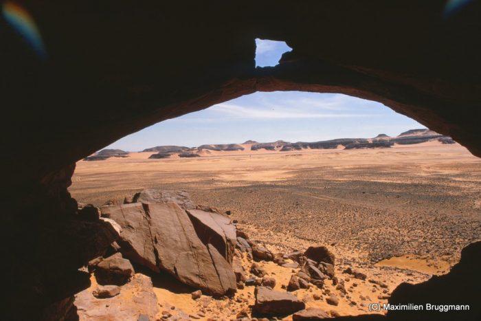 117 Enneri Blaka. Site 10. — L'abri vu de l'intérieur mesure 9,60 m de largeur. Au fond, derrière les montagnes, se trouve le « Sous-marin du Blaka ». Au plafond, on observe un éléphant rouge/rose ; en outre remarquer encore des bovidés, une bête montée... Les sites 7 et 9 se situent dans les rochers en face.