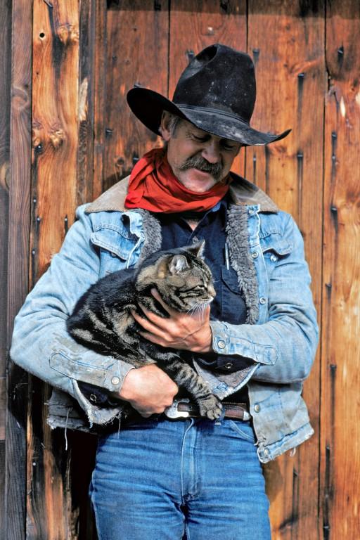 Terry et Misty. Les « vrais » cowboys ne pratiquent guère le rodéo spectacle et préfèrent passer leur été à garder les troupeaux. Sommairement hébergés dans un campement d'altitude, ils ne sont pas autorisés à recevoir leur femme – quand ils en ont une. C'est sans doute pourquoi Terry reporte toute son affection sur son chat Misty. (Rapsberry Camp, Douglas Lake Cattle Ranch, Colombie Britannique, Canada)