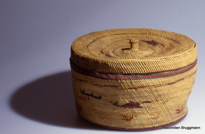 85 A small, densely woven basket with lid. The material is dyed and undyed sweet grass, interwoven to create a scene with water birds and a whaling canoe hunting a killer whale. The basket was acquired from the Makah in 1880. (24 cm; VM)