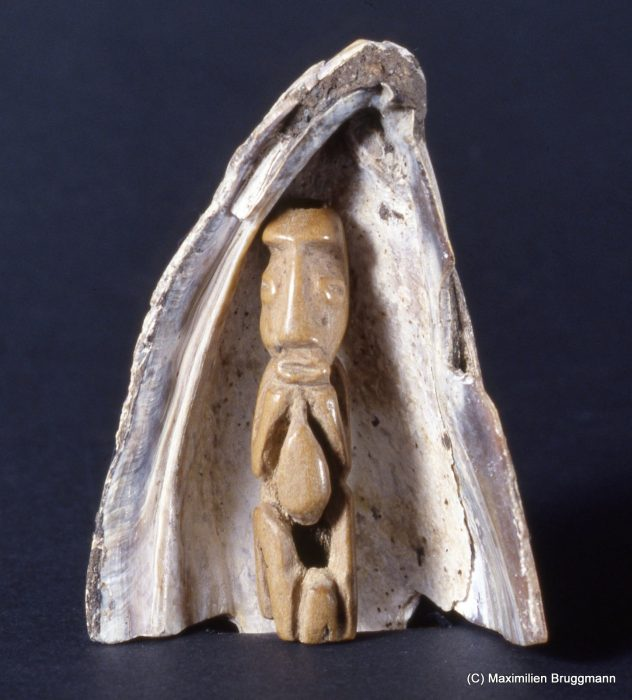 The idea that the first humans lived in a shell is a frequently recurring theme in the various creation myths of the Northwest Coast Indians. This small bone figure, 41 mm (2 inches) high, was dug up together with its protecting shell at Ozette, the archaeological site on the Olympic Peninsula. It is on exhibit at the Makah Museum