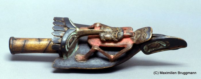 "34 The Tsimshian may have been the first to make raven dance raffles. This example represents a widely disseminated model: On die back of a raven sits a man whose tongue is being pulled out by a frog, which is, in turn, being seized by a kingfisher. The underside of the rattle shows a hawk. ""Underside"" is incorrect in-sofar as this was the side which was on top when a chief held the rattle in his hand. (28 cm; ASM)"
