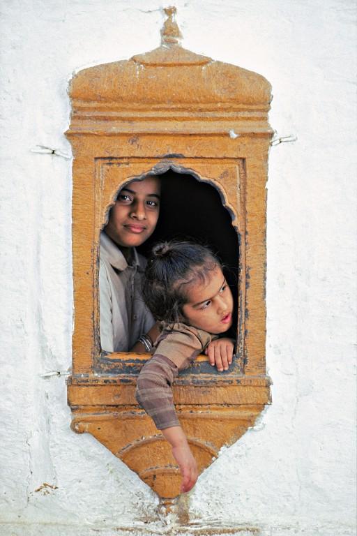 Ne vois-tu rien venir ? A Jaisalmer, à l'ombre de fenêtres minuscules, on a observé pendant des siècles la venue des caravanes, synonymes de richesse et d'ouverture sur le monde. Aujourd'hui, la fermeture de la frontière indo-pakistanaise porte un coup très dur à l'économie locale et même les enfants se demandent si le bonheur reviendra un jour. (Rajasthan, Inde)