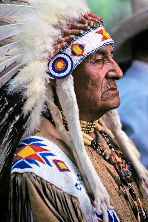 Les plumes de la sagesse. Chef de la tribu amérindienne des Blackfeet. Ils chassaient naguère, à pied et sans armes, les bisons qu'ils affolaient de leurs cris et qui finissaient par se précipiter du haut des falaises. Le nom de Blackfeet provenait sans doute de la couleur noire de leurs mocassins et de leurs jambières.( Etat de l'Alberta, Canada)