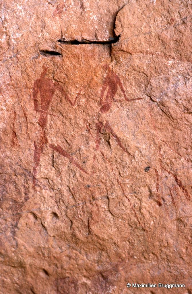 303 Ouan Ouksem (Tadrart). — Abri. Deux person¬nages marchant (en discutant ?) peints à l'ocre rouge. Celui de gauche, du sommet de la tête aux pieds mesure 0,15 m de hauteur.